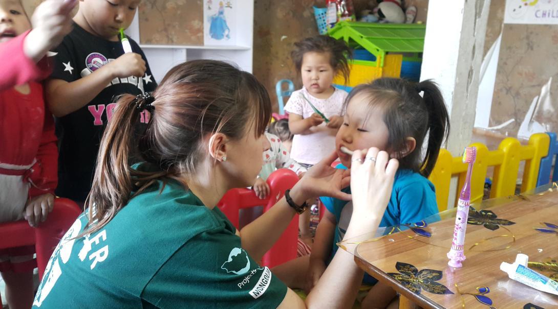 Una voluntaria le enseña a niños cómo cepillarse los dientes en una escuela de Mongolia.